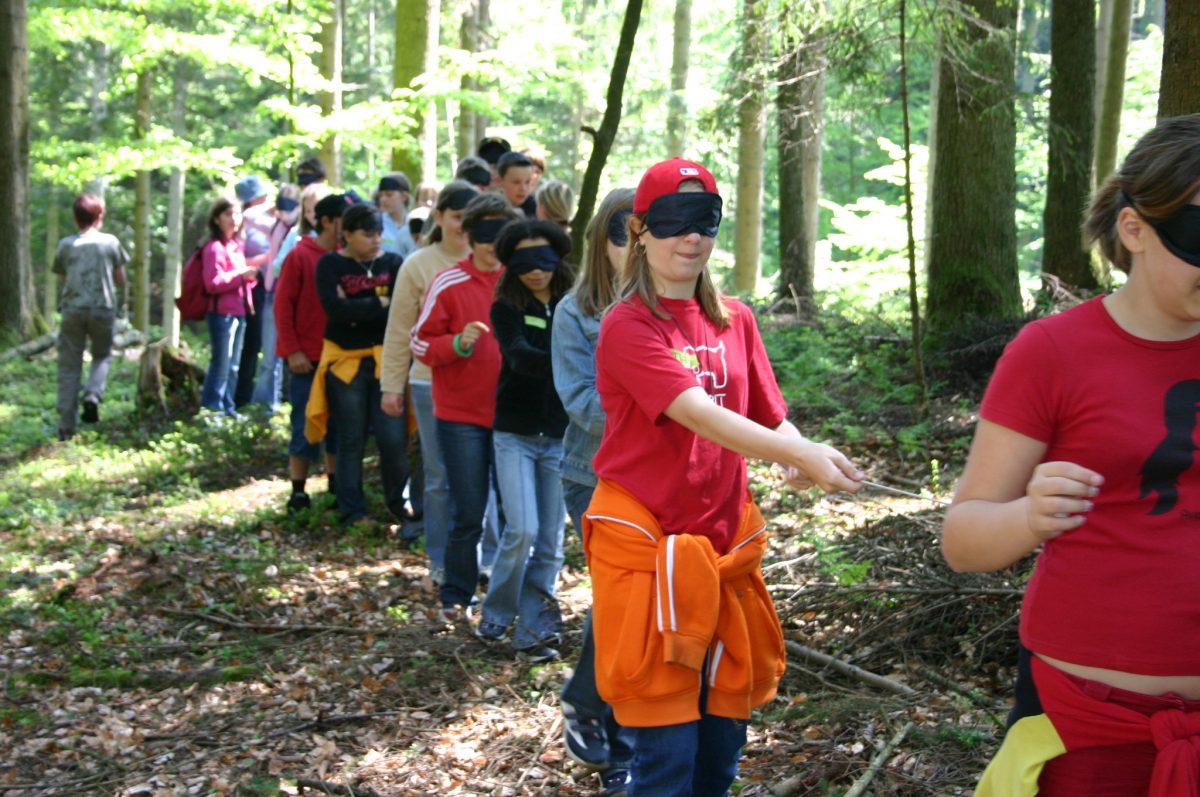 Kinder auf Sinnes erfahrung im Wald mit verdeckten Augen